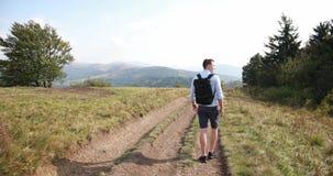 Paseo solo en las montañas El hombre camina a lo largo del camino en una colina con gran paisaje antes de él y mira sobre el suyo almacen de video