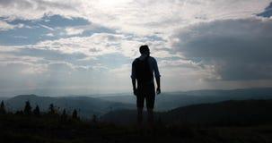 Paseo solo en las montañas Mire de detrás un hombre con la mochila que se coloca antes de paisaje hermoso de la montaña y almacen de video