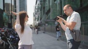 Paseo turístico de la ciudad Los pares de turistas caminan a través de la pieza del negocio de la metrópoli, y admiran el moderno almacen de metraje de vídeo