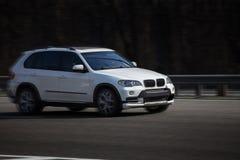 Paseos blancos de BMW en el camino Contra un fondo de árboles borrosos imágenes de archivo libres de regalías