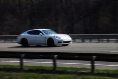 Paseos blancos del panamera de Porsche en el camino Contra un fondo de árboles borrosos fotos de archivo libres de regalías