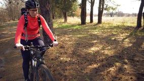 Paseos cauc?sicos de la mujer del deporte del ciclista a lo largo de la pista en el bosque en un d?a soleado de la primavera Mont fotografía de archivo libre de regalías