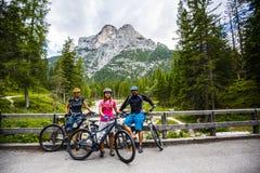 Paseos de la bici de la familia en las montañas imagenes de archivo
