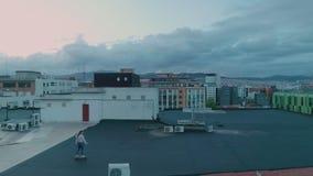 Paseos de la muchacha del patinador en puesta del sol en tejado almacen de video