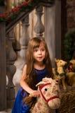 Paseos de la muchacha en el caballo de madera del juguete Imágenes de archivo libres de regalías