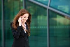 Paseos de la mujer de negocios al aire libre con el smartphone que habla con su equipo Imagen de archivo libre de regalías