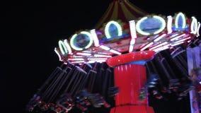Paseos de las luces del bokeh del parque de atracciones del funfair del fondo de las luces del disco de los oscilaciones que muev almacen de metraje de vídeo
