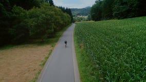 Paseos de los ciclistas en la bici en el camino del campo del bosque almacen de video