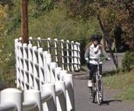 Paseos de un ciclista de la mujer en la caída Foto de archivo libre de regalías