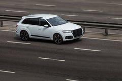 Paseos del blanco de Audi en el camino Contra un fondo de árboles borrosos fotos de archivo