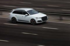 Paseos del blanco de Audi en el camino Contra un fondo de árboles borrosos foto de archivo