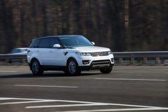 Paseos del blanco de Range Rover en el camino Contra un fondo de árboles borrosos foto de archivo