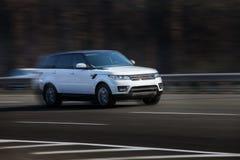 Paseos del blanco de Range Rover en el camino Contra un fondo de árboles borrosos fotografía de archivo
