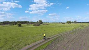 Paseos del ciclista en el prado del verde de la primavera metrajes