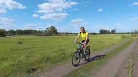Paseos del ciclista en el prado del verde de la primavera almacen de video