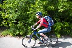 Paseos del ciclista en parque verde Imagenes de archivo