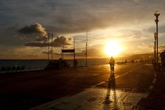 Paseos del ciclista a lo largo de la 'promenade' contra el cielo de la puesta del sol fotografía de archivo