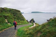 Paseos del hombre joven a lo largo del camino rodeados por paisaje irlandés imágenes de archivo libres de regalías