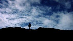 Paseos del hombre sobre silueta del top de la colina almacen de metraje de vídeo