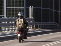 Paseos del motorista en la carretera en un ciclomotor con una mochila Los escudos de los sonidos guardan contra ruido del tráfico fotografía de archivo