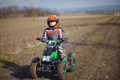 Paseos del muchacho en patio eléctrico de ATV Foto de archivo libre de regalías