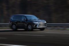 Paseos del negro de Lexus en el camino Contra un fondo de árboles borrosos imagen de archivo libre de regalías