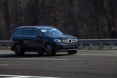 Paseos del negro de Mercedes en el camino Contra un fondo de árboles borrosos imágenes de archivo libres de regalías