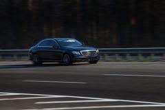 Paseos del negro de Mercedes S en el camino Contra un fondo de árboles borrosos imagen de archivo