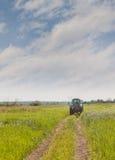 Paseos del tractor en el prado de la primavera Fotos de archivo
