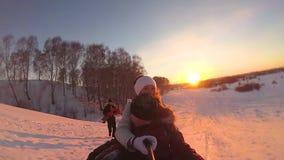 Paseos felices de la familia y snowtube sonriente en los caminos nevosos Cámara lenta Paisaje del invierno de la nieve Al aire li metrajes