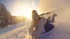 Paseos felices de la muchacha y snowtube sonriente en los caminos nevosos Cámara lenta Paisaje del invierno de la nieve Al aire l metrajes