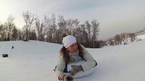 Paseos felices de la muchacha y snowtube sonriente en los caminos nevosos Cámara lenta Paisaje del invierno de la nieve Al aire l almacen de metraje de vídeo