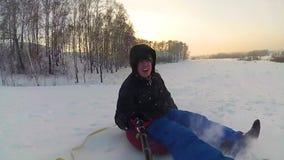 Paseos felices del individuo y snowtube sonriente en los caminos nevosos Cámara lenta Paisaje del invierno de la nieve Al aire li almacen de video