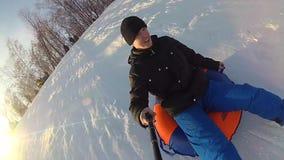 Paseos felices del individuo y sonrisa en el snowtube en la colina nevada y caer almacen de metraje de vídeo