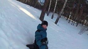 Paseos felices del niño y snowtube sonriente en los caminos nevosos Cámara lenta Paisaje del invierno de la nieve Al aire libre d metrajes