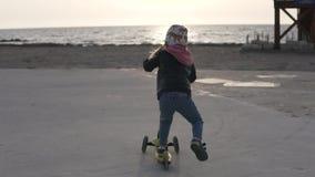 Paseos hermosos de la niña a la playa en una vespa almacen de metraje de vídeo