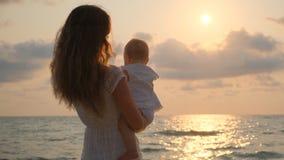 Paseos hermosos jovenes de la mujer con su peque?o beb? en la costa en la puesta del sol almacen de metraje de vídeo