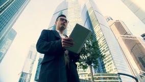 Paseos jovenes del hombre de negocios, mecanografiando en una tableta, visión inferior