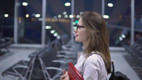 Paseos jovenes, hermosos, sonrientes de la muchacha a lo largo del terminal vacío del aeropuerto, sosteniendo un ordenador portát metrajes