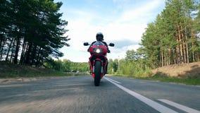 Paseos masculinos del motorista en una bici roja en un camino almacen de metraje de vídeo