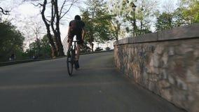 Paseos profesionales fuertes del ciclista ascendentes fuera de la silla de montar Bici pedaling de los músculos atléticos fuertes metrajes
