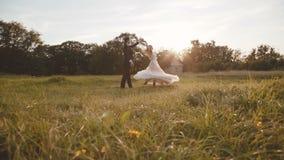 Paseos y giros felices de los pares que se casan en la naturaleza hermosa en el castillo almacen de metraje de vídeo