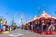Paseos y juegos del carnaval en la feria Imagenes de archivo