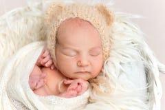 Pasgeboren baby die in grappige bonnet in mand dutten stock foto