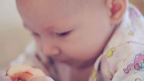 Pasgeboren baby die op het bed liggen en Apple eten stock videobeelden