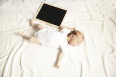Pasgeboren baby en een verjaardagskaart op een lichte achtergrond Royalty-vrije Stock Foto
