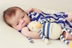 Pasgeboren baby met een gestreept sjaal en een stuk speelgoed, zachte nadrukachtergrond royalty-vrije stock fotografie