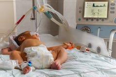 Pasgeboren baby met hyperbilirubinemia bij de ademhaling van machine met de sensor van impulsoximeter en perifere intraveneuze ca stock foto