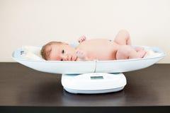 Pasgeboren baby op het wegen schaal Royalty-vrije Stock Foto