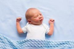 Pasgeboren babyjongen op een blauwe deken Stock Afbeeldingen
